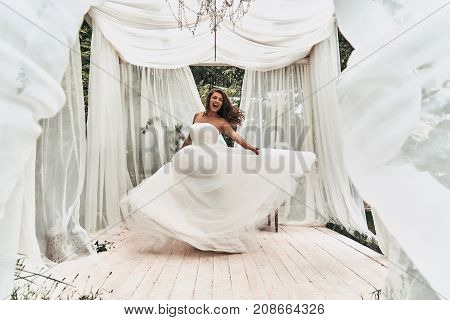 Impossible to hide her happiness. Full length of attractive young woman in wedding dress shouting while dancing in the wedding pavilion outdoors