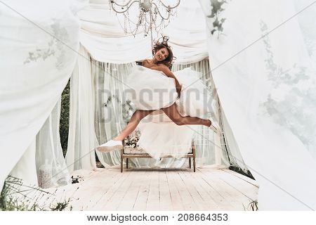 Celebrating her special day. Full length of attractive young woman in wedding dress and sports shoes smiling while jumping in the wedding pavilion outdoors