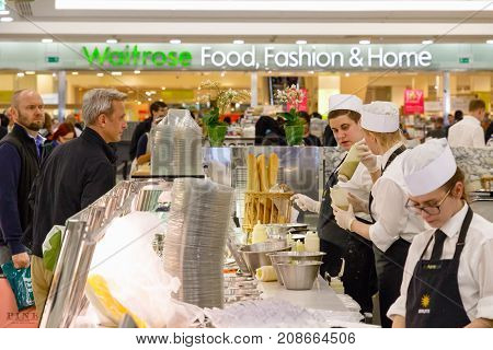 London UK - June 25 2017 - Staff serving customers at a food bar in Canary Wharf with Waitrose supermarkets in the background