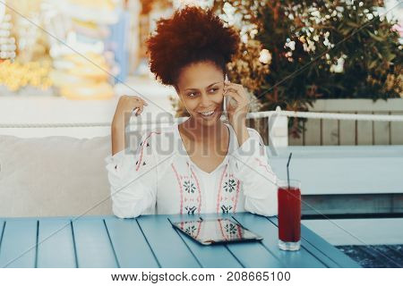 Portrait of skittish black girl sitting at the table of cafe outdoors and talking on the phone; smiling naughty young biracial woman in street bar with digital pad cell phone and glass of red juice