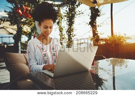Charming young African American woman entrepreneur is sitting alone at the glass table of luxury street restaurant and having remote online video session with colleagues using laptop warm sunny day