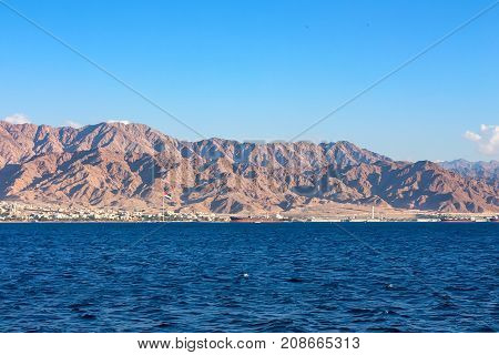 Coastline landscape of the Red Sea in the Gulf of Aqaba with Jordan flag