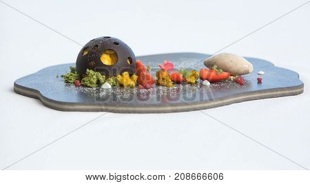 Mango dessert with chocolate and strawberry slices on a plate