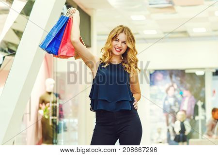 Happy Elegant Woman With Shopping Bags Is Looking At Camera And Smiling While Doing Shopping In The
