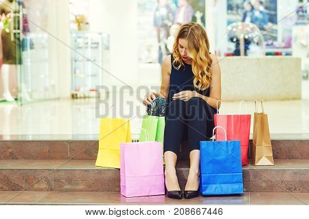 Beautiful Young Woman Sit On Stairs After Shopping With Shopping Bags In Store.