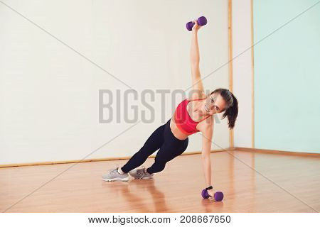 Pretty young woman doing side planks with dumbbells at gym.