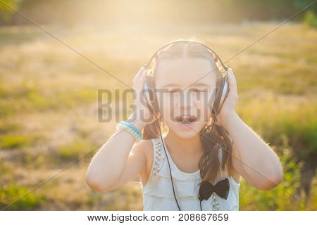 pretty girl listening music with headphones and joyfully singing, cute child resting on nature