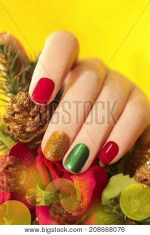 Multicolor manicure with red,green and yellow brilliant varnish for the nails on a yellow background with rose and Christmas tree.
