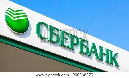 Samara Russia - October 08 2017: Sign with the logo office of the Russian Sberbank against the blue sky. Largest russian bank. Text in russian: Sberbank