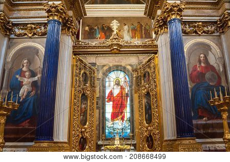 ST PETERSBURG RUSSIA - AUGUST 15 2017. Interior of the St Isaac Cathedral in St Petersburg Russia. Stained glass window with Bible paintings and interior decoratios