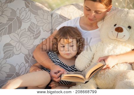 Family leisure time. Mother reading to her toddler daughter. Little girl loves to read.