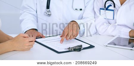 Doctor and  patient talking while sitting at the desk in office. Physician pointing into medical history form. Medicine and health care concept.