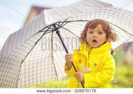 Toddler Girl Wearing Yellow Waterproof Coat  With Chekered Umbrella