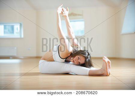 Beautiful woman practices yoga asana paschimottanasana - seated forward bend in the yoga studio.