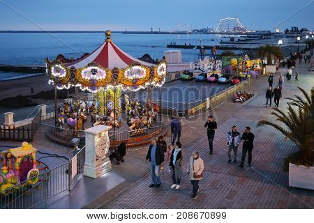 SOCHI, RUSSIA - MAY 4, 2017: People walk on seaside promenade with attractions, during 2016 Sochi was visited by more than 5.2 million tourists