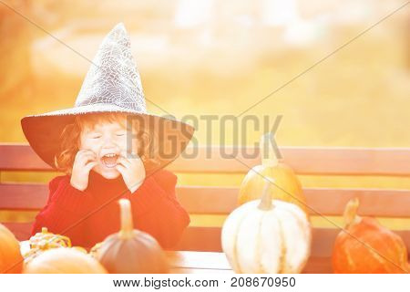 Happy little child with pumpkins having fun. Halloween decorations warm toned greeting card.