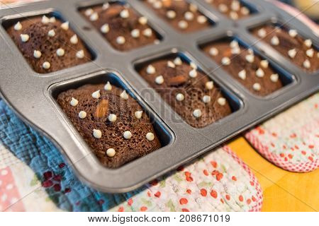 Brownie chocolate cake with nut on hot tray plate on the wood table.