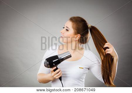 Woman Drying Her Hair Using Hair Dryer