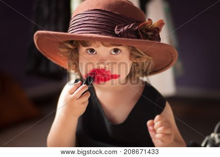 Little girl making makeup with mother cosmetics. Learning to be a woman.