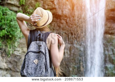 Girl In The Hat Admires The Waterfall. View From The Back