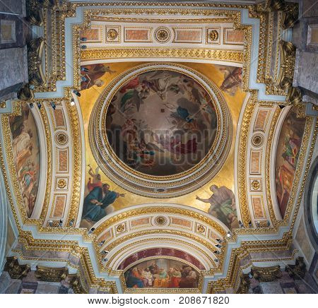 ST PETERSBURG RUSSIA - AUGUST 15 2017. Icons and dome ornated with Bible scenes in the interior of the St Isaac Cathedral in St Petersburg Russia. Inside view of St Petersburg landmark