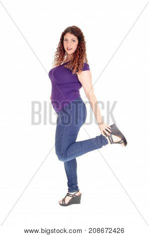 A young woman standing in jeans and sweater in profile holding her leg up with curly hair isolated for white background
