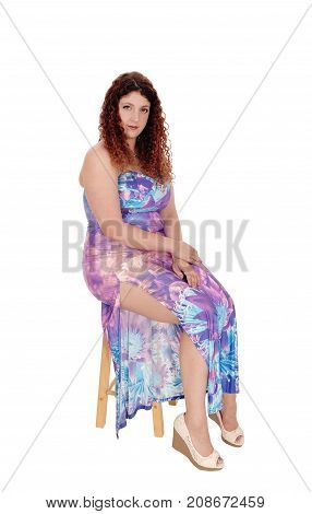 A lovely young woman sitting in a long colorful dress on a bar chair with long curly brunette hair isolated for white background