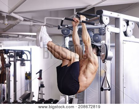 asian bodybuilder exercising abdominal muscle by hanging himself on equipment.