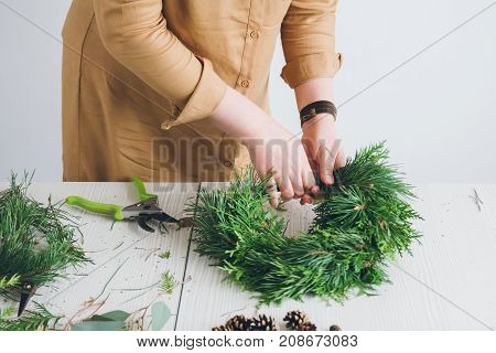 Florist decorator making Christmas wreath handmade on a white table. Women's hobby. Preparations for the holidays concept.