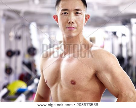 portrait of a young asian bodybuilder in fitness center.