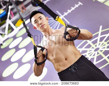 asian bodybuilder working out in gym using fitness straps.