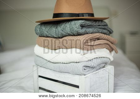 Autumn. Cozy. Knitted Warm Clothes. Home Comfort. Warm Autumn. Sweaters And Hat In A Wooden Box.