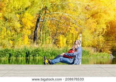 Father and son are sitting on the dock. Autumn sunny. Side view