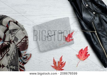Gray Sweater With The Inscription, A Black Jacket, Scarf And Autumn Leaves. Fashionable Concept
