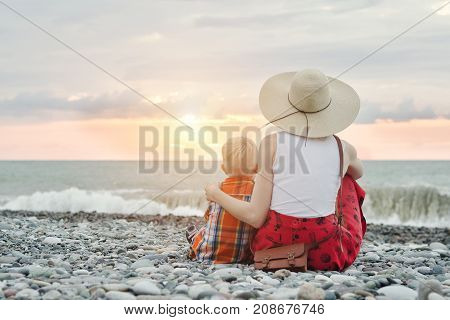 Mom And Son Sitting On The Ocean Shore. View From The Back