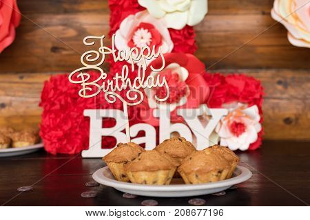 Birthday cakes, muffins with wooden greeting signs on rustic background. Wooden sing with letters Happy Birthday, Baby and holiday sweets