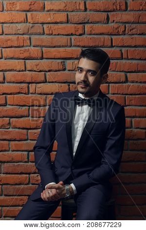 Young Handsome Man In Elegant Suit With Butterfly On The Brick Wall Background.