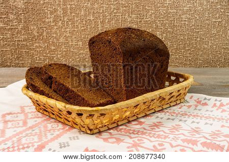 Sliced Rye Bread In A Basket Standing On A Towel. A Loaf Of Fresh Rye Bread With Slices On A Wooden