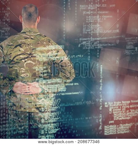 Rear view of soldier standing with his hands behind back against abstract black room