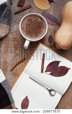 Rural wooden background with pumpkin and autumn leaves, a cup of pumpkin latte with coffee or cocoa, a notebook, a plaid in a cage, top view. Autumn background.