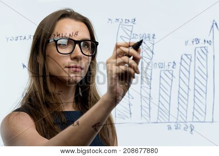 Businesswoman draws various growth charts calculating prospects for success in a modern glass office