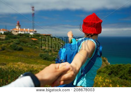Follow me - happy young woman in a red hat and with a backpack behind her back pulling guy's hand. Hand in hand walking to the lighthouse. Concept of carefree modern life