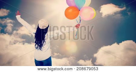 Full length rear view of carefree woman holding colorful balloons against sky