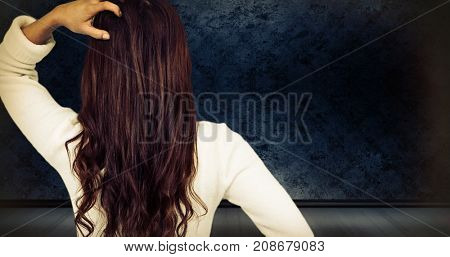 Rear view of confused woman with hand in hair  against dark grimy room