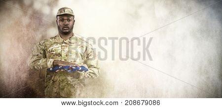 Portrait of soldier holding American flag against dark background