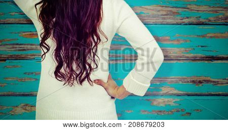 Rear view of confused woman with hand in hair  against horizontal wood panelling