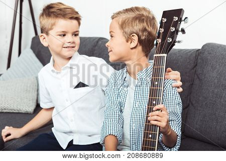 cute little little brothers holding guitar and smiling each other at home
