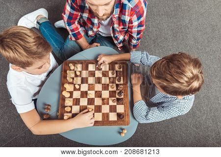 overhead view of father with sons playing chess at home