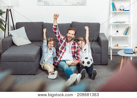 cheerful father with sons raising hands while watching soccer match at home