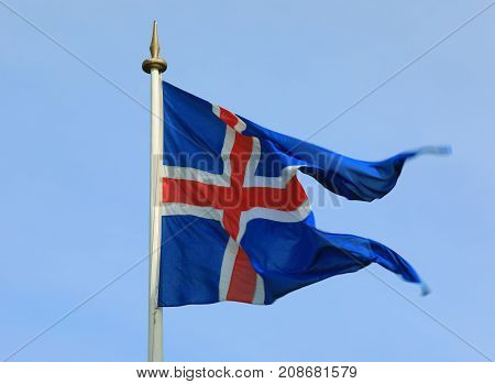 Iceland flag waving on the wind against a blue sky